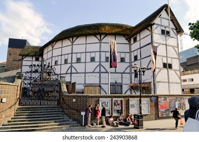 LONDON - JULY 1, 2014. People passing by in front of posters advertising plays at The Globe Theater. The theater is a reconstruction of Shakespeare's original globe, opened for performances in 1997.