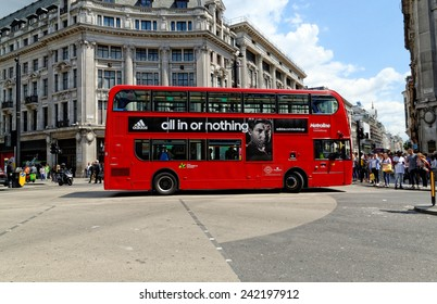 LONDON - JULY 1, 2014: A London red bus bearing Adidas advertisement crossing at Oxford Circus in London.