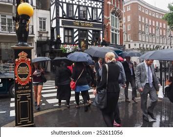 LONDON - JULY 2013:  Londoners carry their umbrellas on a rainy day in front of the 18th century George tavern across the street from the Royal Court of Justice in July 2013.