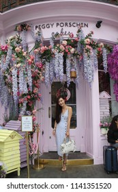 LONDON - JULY 2018: A fashionable young Asian woman leaves the English cake shop Peggy Porschen Cakes in July 2018 in London. The shop is located in London's Belgravia neighborhood.