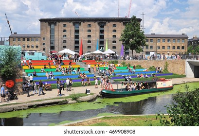 LONDON - JULY 23, 2016. Visitors relax on the terraces at Granary Square overlooking the Regent's Canal, part of the ongoing regeneration of the King's Cross area in the Borough of Camden, London.