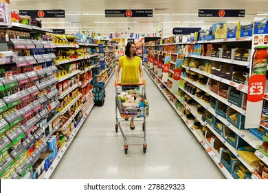 LONDON - JUN 14: A shopper browses an aisle at a Sainsbury's supermarket on Jun 14, 2014 in London, UK. Sainsbury's is the UK's second largest supermarket with a revenue of £23 billion in 2013.