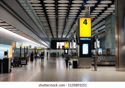 LONDON - JUNE 14, 2018: Passengers at the baggage collection hall in Terminal 5, Heathrow Airport, London. Heathrow is the main airport serving London.