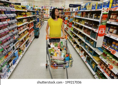 LONDON - JUNE 14: A shopper browses an aisle at a Sainsbury's supermarket on June 14, 2014 in London, UK. Sainsbury's is the UK's second largest supermarket with a revenue of �£23 bln in 2013.