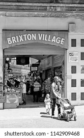 LONDON - JUNE 18, 2018: Shoppers at Brixton Village entrance in Atlantic Rd, Brixton, South London. Brixton Village is part of the famous Brixton Market selling a range of Afro-Caribbean products.