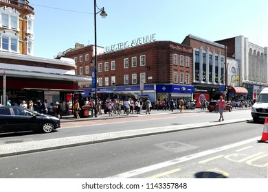 LONDON - JUNE 18, 2018: View of junction into Electric Avenue from Brixton Road, Brixton, South London. The market street built in the 1880s was the first market street to be lit by electricity.