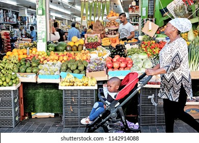 LONDON - JUNE 18, 2018: A woman walks by a fruit stall in Brixton Market in Electric Avenue, Brixton, South London. The market st built in the 1880s is famous for its range of Afro-Caribbean products.