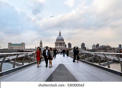 LONDON - JUNE 20: People walking over Millennium bridge on June 20, 2014 in London, UK. It's a suspension bridge with a total length of 370 metres (1,214 ft) and a width of 4 metres (13 ft).