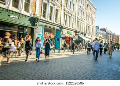 LONDON- JUNE, 2018: Shopping street with motion blurred people walking outside South Kensington tube station