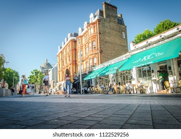 LONDON- JUNE, 2018: Wide angle view of South Kensington street with outdoor restaurants and motion blurred people walking