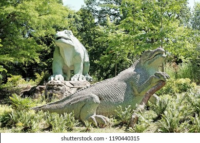 LONDON - JUNE 27, 2018: Iguanodon sculptures in Crystal Palace Park in Crystal Palace, London. The sculptures unveiled in 1854 are the world first dinosaur sculptures and are Grade I listed.