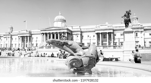 LONDON - JUNE 29, 2018: Panoramic view of the Merman and dolphins statue in Western Trafalgar Square fountain, Trafalgar Square, London. The memorial sculptures were added to the fountain in 1948.