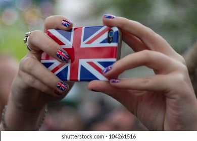 LONDON - JUNE 3: A camera phone is lifted above the crowds to capture a photo as crowds celebrate Thames Diamond Jubilee Pageant on June 3, 2012 in London.