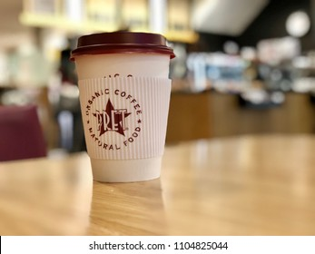 LONDON - JUNE 4, 2018: A disposable paper coffee cup on a table inside Pret A Manger coffee shop in London, UK.