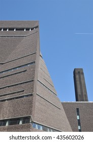 LONDON - JUNE 6, 2016. The angular perforated brickwork of the Tate Modern art gallery extension, designed by Herzog & de Meuron, with the original power station chimney beyond at Bankside, London.