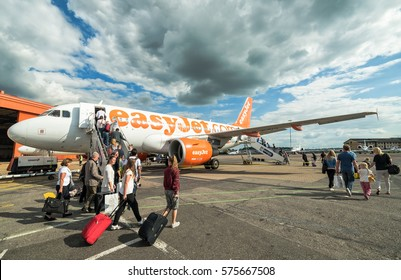 LONDON LUTON, UK - 14 JULY 2016: People boarding to Easy Jet plane on London Luton Airport. Easy Jet operates over 200 aircraft and it's the second biggest low-cost airline company in Europe.