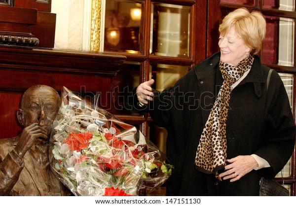 London. Maggie Smith lays a wreath  on Noel Coward's statue in the foyer of the Theatre Royal, Drury Lane, for his birthday celebration.  17 December 2005. Ali Kadinsky/Landmark Media