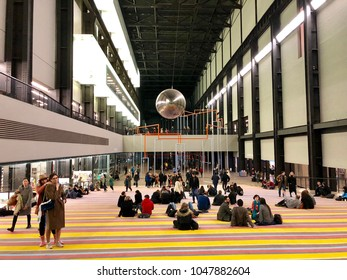 LONDON - MARCH 16, 2018: Visitors interact with the 'One Two Three Swing!' exhibtion by Danish artists' collective SUPERFLEX inside the Turbine Hall of Tate Modern art gallery in Bankside, London, UK.