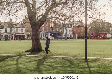 LONDON- MARCH, 2018: Female runner exercising on Wandsworth Common, south west London, with Bellevue Road in background.