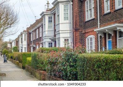 LONDON- MARCH, 2018: Pedestrians walking past a row traditional terrace houses close to Earlsfield station in south west London