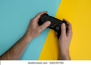 LONDON - MARCH 22, 2018: Man playing video games holding PlayStation gaming controller in hands