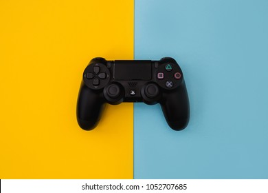 LONDON - MARCH 22, 2018: Video games PlayStation gaming controller isolated on yellow blue background