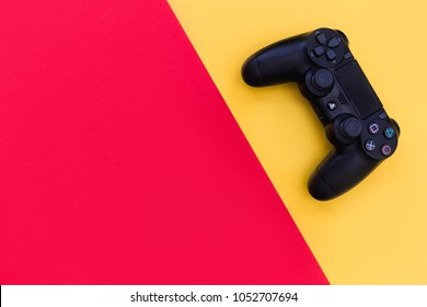 LONDON - MARCH 22, 2018: Video games PlayStation gaming controller isolated on yellow red background