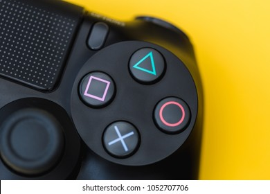 LONDON - MARCH 22, 2018: Video games PlayStation gaming controller isolated closeup on bright yellow background