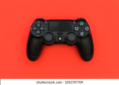 LONDON - MARCH 22, 2018: Video games PlayStation gaming controller isolated on bright red background