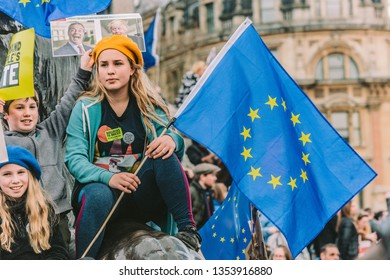 London - March 23, 2019 - People's Vote March - A Young Pro-EU Protester sits defiantly upon one of the bronze lions in Trafalgar Square