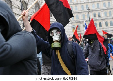 LONDON - MARCH 26: A breakaway group of anarchist protesters march through the streets of the British capital during a large anti-cuts rally on March 26, 2011 in London, UK.