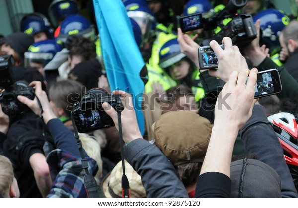 LONDON - MARCH 26: Journalists jostle for position to photograph protesters clashing with riot police during a large austerity rally on March 26, 2011 in London, UK.