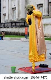 LONDON - MARCH 31, 2018. A street performer, dressed as the Star Wars character Yoda, apparently floats in Trafalgar Square, a popular tourist venue in central London, UK.