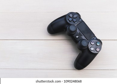 LONDON - MAY 03, 2018: Video games PlayStation gaming controller on wood background