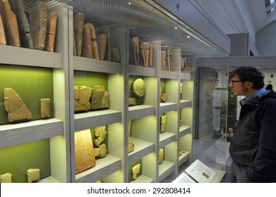 LONDON - MAY 15 2015:Visitor in the British Museum look at cuneiform tablets.Almost 2M cuneiform tablets have been excavated of which only approximately less then 100,000 have been read or published.