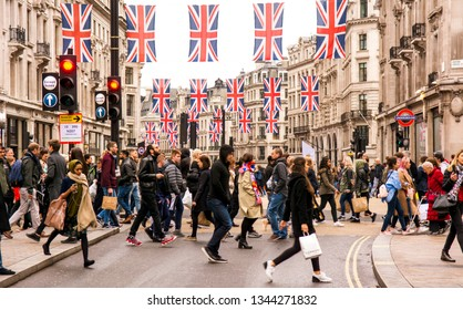 LONDON- MAY, 2018: Busy London street scene at Oxford Circus with British flags decorating Regent Street, a landmark retail destination in London's West End