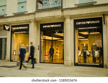 LONDON- MAY, 2018: Motion blurred shoppers walking past the Emporio Armani store on Bond Street, an upmarket shopping street in London