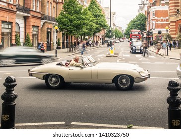 LONDON- MAY, 2019: An E Type Jaguar classic car driving on Sloane Square in Chelsea / Knightsbridge, an upmarket area of luxury shops and restaurants