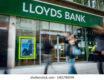 LONDON- MAY, 2019: Lloyds bank exterior with motion blurred people. A British high street retail and commercial bank.