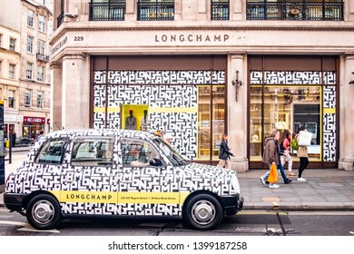 LONDON- MAY, 2019: Longchamp luxury French fashion brand store. Flagship store on Regent Street with Longchamp advertisement on taxi driving past.