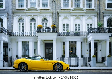 LONDON, MAY, 2019: A yellow Ferrari parked outside attractive townhouses in Knightsbridge, an affluent area of London.