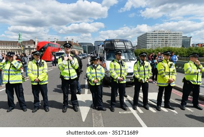 LONDON - MAY 30: Police officers stand guard during a rally protesting government public sector spending cuts following the re-election of the conservative party on May 30, 2015 in London, UK.