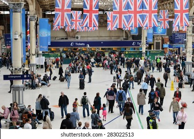 LONDON - MAY 30: Travellers walk through Victoria train station on May 30, 2015 in London, UK. Victoria is the second busiest train station in the UK with 73 million passengers entry and exits.