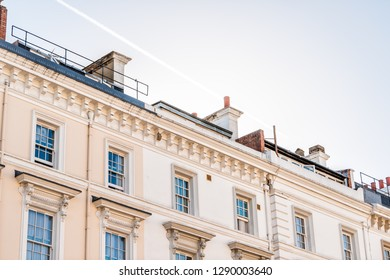 London neighborhood district of Pimlico with terraced housing balconies buildings old vintage historic traditional style flats roof with chimneys sun and sky