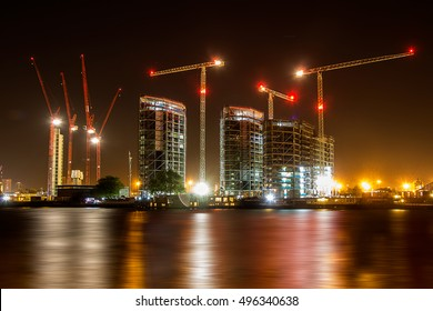 London Nine Elms development in construction along the river Thames and taken at night with reflections in the water.