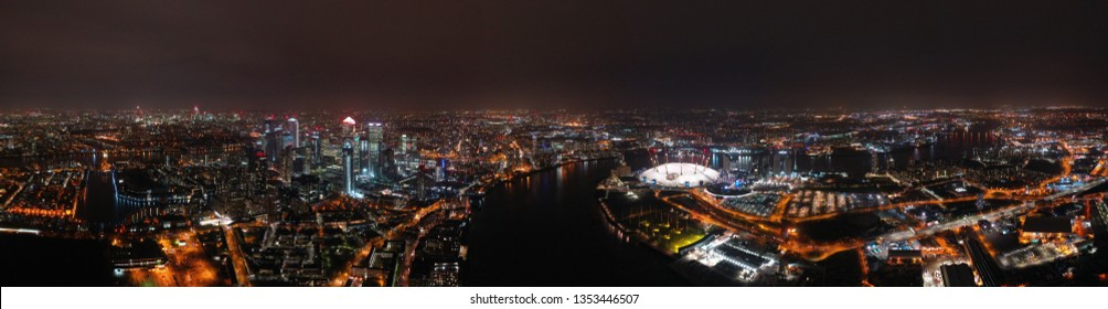 London, North Greenwich / United Kingdom: March 15 2019: Aerial night panoramic shot from iconic O2 Arena in Greenwich Peninsula and Canary Wharf skyscraper area in isle of dogs