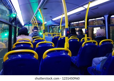 LONDON - NOV 13 : Inside view of London Double Decker bus at night. Rows of empty blue seats and commuters present on Nov 13, 2018, London, UK.