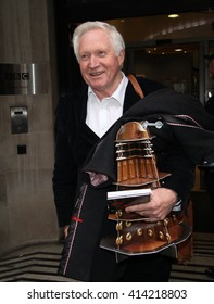 LONDON - NOV 22, 2013: David Dimbleby seen leaving the BBC radio two studio carrying a cut out Dr Who Dalek on Nov 22, 2013 in London