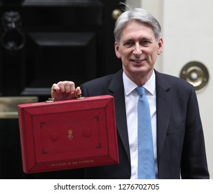 LONDON - NOV 22, 2017: Chancellor of the Exchequer, Philip Hammond, holds the famous red box on the steps of Number 11 Downing street