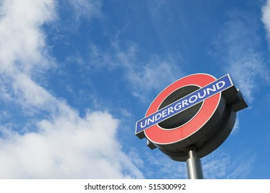 LONDON - NOVEMBER 14, 2016: Classic London Underground roundel sign, an icon credited to the manager Frank Pick in the early 1900s, under bright blue sky.